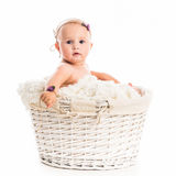 Cute little baby in a wicker Stock Images