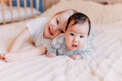 Free Cute Little Baby With Elder Brother Lying On Bed At Home Stock Images - 129134804