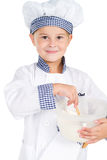 Cute little baker. Cute little girl in baker uniform mixing flour, studio shot isolated on white Royalty Free Stock Photos