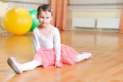 Cute little balerina stretching on floor Stock Photography