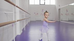 Cute little ballerina in leotard whirling in dance at ballet school. Cute little ballerina whirling in dance at ballet school. Adorable little girl learning stock video footage