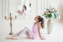 A cute little ballerina in a pink ballet costume and pointe sitting on the floor. Ballerina in the dance class. The girl is studyi royalty free stock image