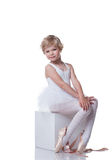 Cute little ballerina sitting on cube in studio Stock Images