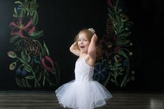 Cute little ballerina in white ballet costume is dancing in the room. Kid in dance class. Child girl is studying ballet. Copy space Royalty Free Stock Images
