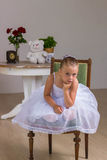 Cute little ballerina in a white dress sitting Stock Photography