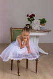 Cute little ballerina in a white dress sitting Stock Photos