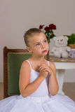 Cute little ballerina in a white dress sitting on wooden chair Royalty Free Stock Photo