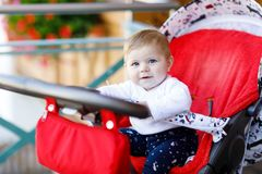 Cute little beautiful baby girl of 6 months sitting in the pram or stroller and waiting for mom Stock Image
