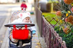Cute little beautiful baby girl sitting in the pram or stroller on autumn day. Happy healthy child going for a walk on stock photography
