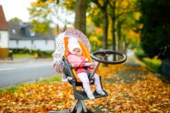 Cute little beautiful baby girl sitting in the pram or stroller on autumn day. Happy healthy child going for a walk on royalty free stock photos