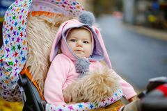 Cute little beautiful baby girl sitting in the pram or stroller on autumn day. Happy smiling child in warm clothes royalty free stock photo