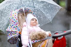 Cute little beautiful baby girl sitting in the pram or stroller on cold day with sleet, rain and snow. Happy smiling child in warm clothes, fashion stylish Stock Photos