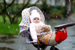 Cute little beautiful baby girl sitting in the pram or stroller on cold day with sleet, rain and snow. Happy smiling child in warm clothes, fashion stylish Royalty Free Stock Photography