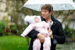 Cute little beautiful baby girl and young father on cold day with sleet, rain and snow. Happy smiling child in warm clothes, fashion stylish baby coat. Baby Royalty Free Stock Photos