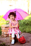 Cute little beautiful girl  with pink umbrella and handbag in park Stock Images