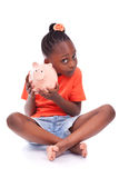 Cute little black girl holding a smiling piggy bank - African ch. Cute little black girl holding a smiling piggy bank, isolated on white background - African Stock Photo