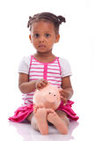 Cute little black girl holding a smiling piggy bank - African ch. Cute little black girl holding a smiling piggy bank, isolated on white background - African Royalty Free Stock Photography