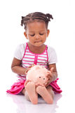 Cute little black girl holding a smiling piggy bank - African ch Stock Images