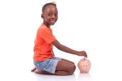 Cute little black girl inserting an euro bill inside a piggy ban. K, isolated on white background - African children Stock Photo