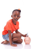 Cute little black girl inserting an euro bill inside a piggy ban. K, isolated on white background - African children Stock Images