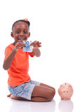 Cute little black girl inserting an euro bill inside a piggy ban. K, isolated on white background - African children Royalty Free Stock Image