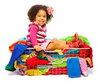 Black girl in fashion basket. Cute little black girl sitting in the basket full of clothes with fuzzy hair and smile on her face, isolated on white Royalty Free Stock Photo
