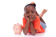 Cute little black girl with a smiling piggy bank - African child. Cute little black girl with a smiling piggy bank, isolated on white background - African Stock Photography