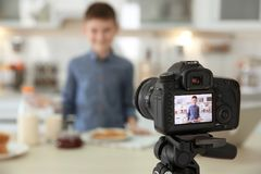 Cute little blogger with food on camera screen,. Closeup stock photo