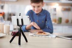 Cute little blogger with food recording video. On kitchen royalty free stock images