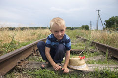 Cute little blond boy playing on railway Stock Photo