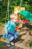 Cute little blond boy swinging on swings outdoor playground royalty free stock images