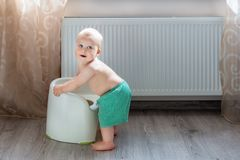 Cute little blond caucasian boy in funny green shorts playing with white potty indoor. Adorable child learning about potty-chair d royalty free stock photos