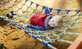 Cute little blond caucasian boy having fun on outdoor playground. Active sport leisure for kids. Child on hammock royalty free stock photos