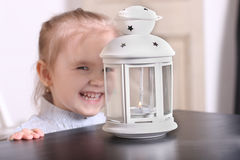 Cute little blond girl laughing before luminaire with candle. Fo Royalty Free Stock Image