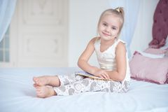 Cute little blond girl lying on bed. Cute little blond girl sitting on a bed looking up into the air with a happy expression as she watches something Stock Image