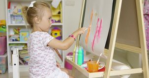 Cute little blond girl painting with watercolors stock footage