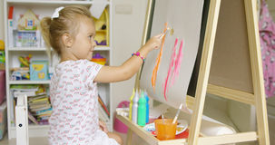 Cute little blond girl painting with watercolors Royalty Free Stock Image