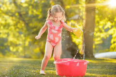 The cute little blond girl playing with water splashes on the field in summer Royalty Free Stock Photos