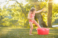 The cute little blond girl playing with water splashes on the field in summer Stock Images