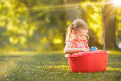 The cute little blond girl playing with water splashes on the field in summer Stock Photos