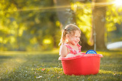 The cute little blond girl playing with water splashes on the field in summer Royalty Free Stock Images