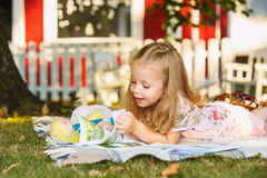 Cute Little Blond Girl Reading Book Outside on Grass Royalty Free Stock Image