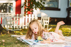 Cute Little Blond Girl Reading Book Outside on Grass Royalty Free Stock Photos