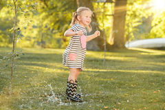The cute little blond girl in rubber boots playing with water splashes on the field in summer Royalty Free Stock Photos