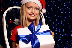 Cute little blond girl in santa hat and red dress holding a gift - box on the background of holiday shining ligh Royalty Free Stock Images