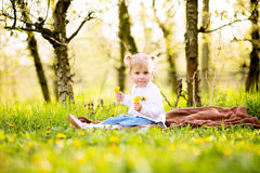 Cute little blond girl sitting on a blanket in a grass in orchar Stock Images