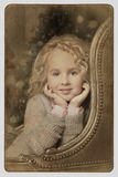 Cute little blond girl sitting peering over chair arms. A cute little blond girl with long hair sitting peering over chair arms in a classic style at the camera Royalty Free Stock Images