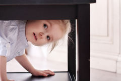 Cute little blond girl in striped shirt climbed in recess table Royalty Free Stock Images