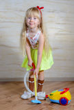 Cute little blond girl vacuuming house Stock Photos