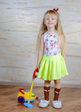 Cute little blond girl vacuuming the house Royalty Free Stock Image